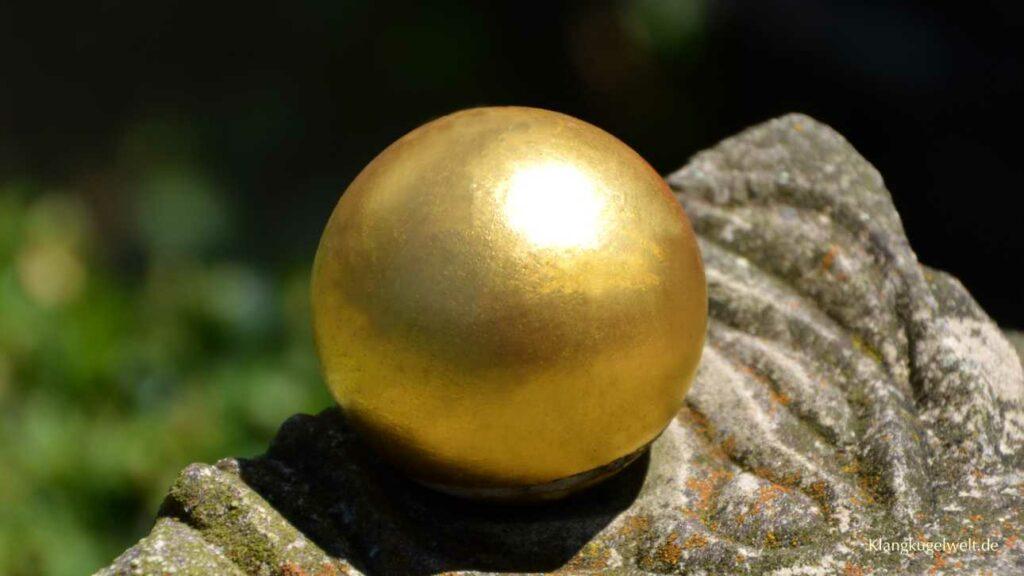 Eine goldene Kugel liegt auf einem verwitterten Stein.