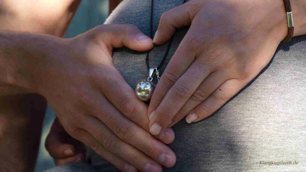 Auf dem Bauch einer schwangeren Frau liegen die Händen von einem Mann und einer Frau.