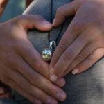 Die Hände von einem Mann und einer Frau liegen auf einem Schwangerschaftsbauch